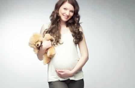беременная стоит с игрушкой