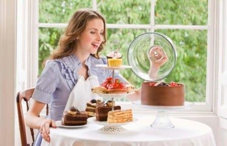 девушка сидит за столом со сладостями