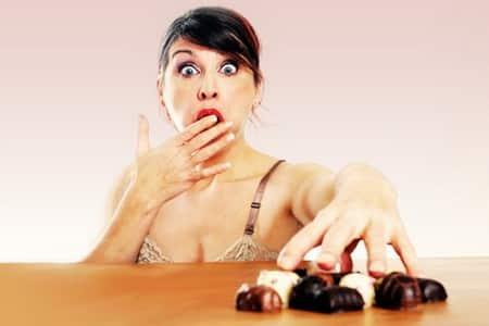 Женщина ест конфеты