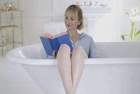 женщина читает книгу сидя в ванной